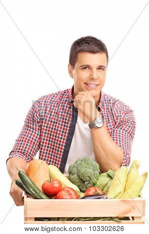 Young man leaning on a wooden crate full of fresh vegetables and looking at the camera isolated on white background