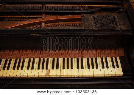 black and white piano keys and wood grain with vintage sepia tone one ragged keys..