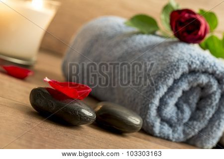 Romantic Atmosphere With A Red Rose On Top Of Rolled Towel, Lit Candle And Black Massage Stones