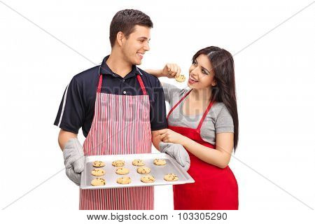 Studio shot of a young couple holding an aluminum pan with chocolate chip cookies isolated on white background