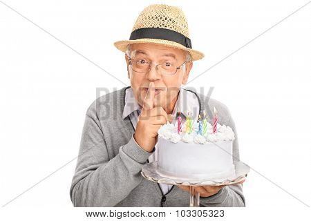 Senior gentleman carrying a birthday cake and holding a finger on his lips isolated on white background