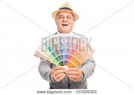 Joyful senior gentleman holding a color palette swatch and looking at the camera isolated on white background
