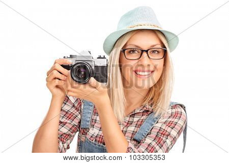 Blond female photographer with a blue cap holding a camera and posing isolated on white background