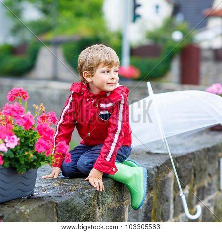 Little Blond Kid Boy With Big Umbrella Outdoors