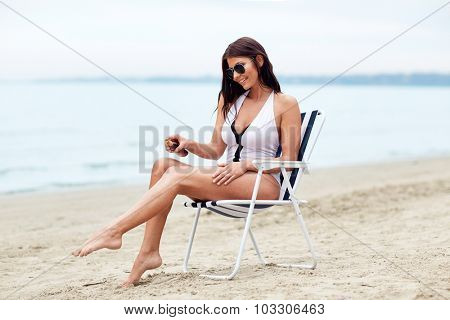 summer vacation, tourism, travel, holidays and people concept - close up of young woman in swimsuit sunbathing on folding chair and spraying sunscreen oil to her skin