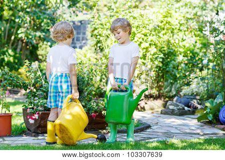Two Little Kid Boys Watering Plants In Greenhouse In Summer
