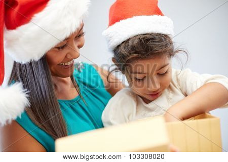 christmas, holidays, family, childhood and people concept - happy mother and little girl in santa hats opening gift box at home