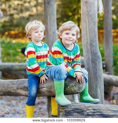 Two Little Kid Boys Having Fun On Autumn Playground