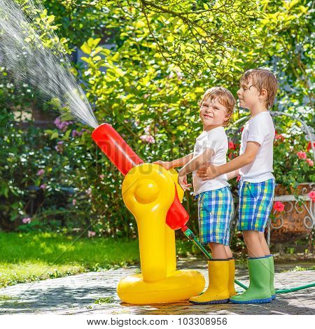 Two Little Kids Playing With Garden Hose And Water In Summer