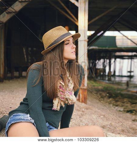 Beutiful woman sitting under pier.