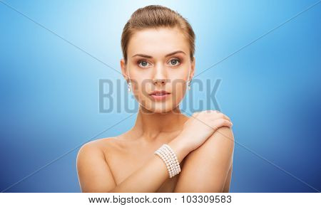 beauty, luxury, people, holidays and jewelry concept - beautiful woman with pearl earrings and bracelet over blue background