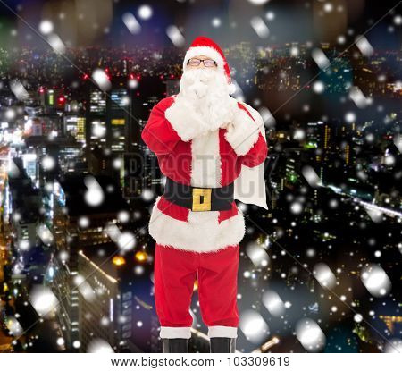 christmas, holidays and people concept - man in costume of santa claus with bag making hush gesture over snowy night city background