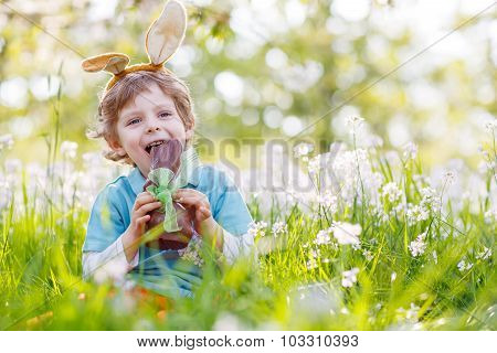 Little Toddler Wearing Easter Bunny Ears And Eating Chocolate At