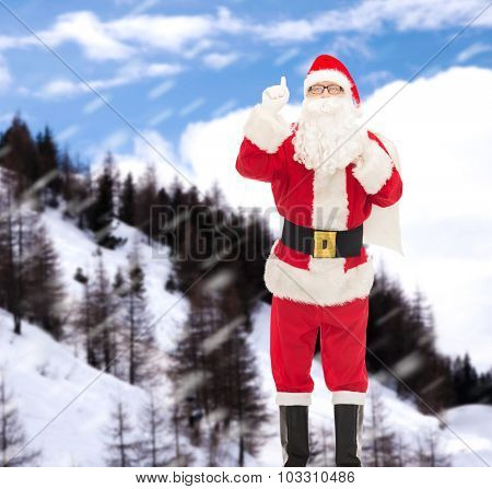 christmas, holidays, gesture and people concept - man in costume of santa claus with bag pointing finger up over snowy mountains background