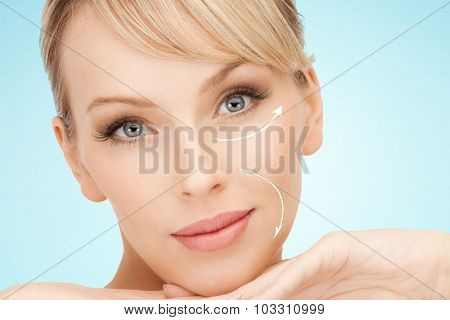 beauty, people, anti-aging treatment and plastic surgery concept - beautiful young woman with face lifting arrows over blue background