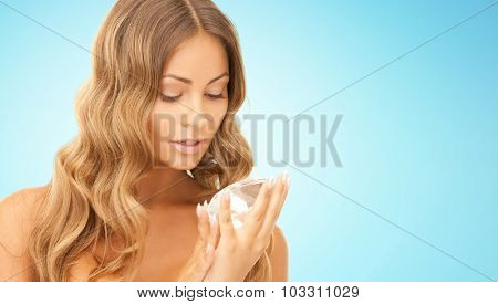 people, jewelry, luxury and beauty concept - woman holding big diamond over blue background