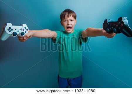 Teen  boy of twelve European  appearance holds a gaming zhdoysti