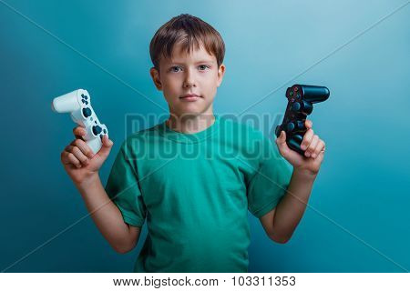 Teen  boy of twelve European appearance holds a gaming zhdoystik