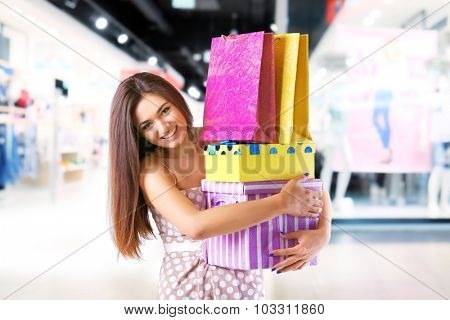 Beautiful young woman with shopping bags and boxes in the mall