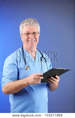 Doctor with clipboard on blue background