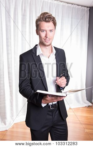 Portrait Young Business Man In Suit Taking Notes Into Book