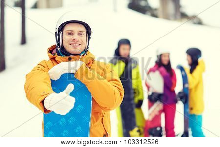 winter, leisure, extreme sport, friendship and people concept - happy young man in helmet with snowboard and group of friends showing thumbs up