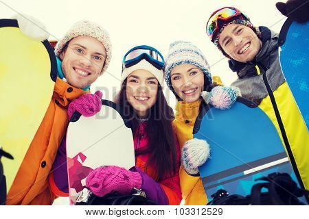 winter, leisure, extreme sport, friendship and people concept - happy friends with snowboards