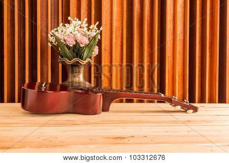 Vase Of Flowers Ukulele And Wood Background