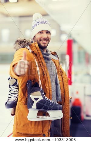 people, sport, gesture and leisure concept - happy young man with ice-skates showing thumbs up on skating rink