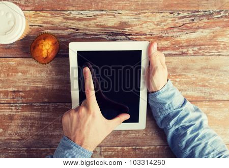 business, education, people and technology concept - close up of male hands with tablet pc computer, muffin and coffee cup on table