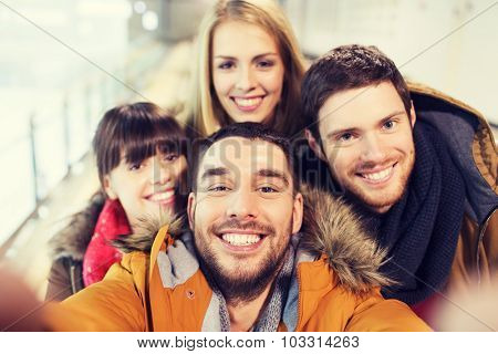 people, friendship, technology and leisure concept - happy friends taking selfie with camera or smartphone on skating rink
