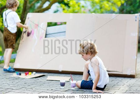 Two Little Kid Boys Painting Big Paper House With Colorful Paint