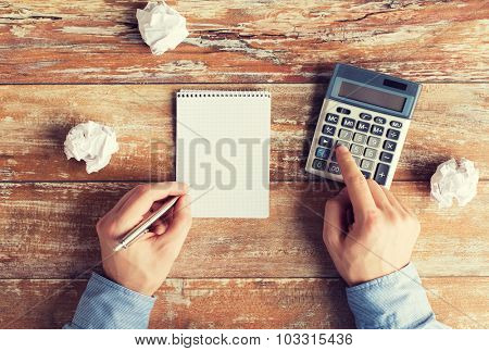 business, education, people and technology concept - close up of close up of male hands with calculator, cramped paper wads and notebook on table