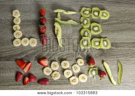 The Word Life Written With Fruits On A Wooden Background.