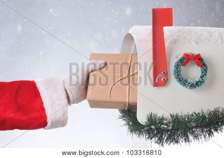 Santa Claus putting a plain brown paper wrapped package in a mailbox. Horizontal format with a snowy background.