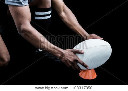 Cropped image of sportsman keeping rugby ball on kicking tee against black background