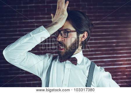 Frustrated man with head in hand against brick wall