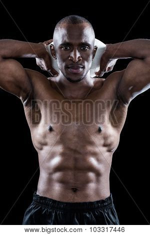 Portrait of shirtless sportsman holding rugby ball behind head standing against black background