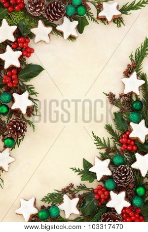 Christmas gingerbread star biscuit abstract background border with green bauble decorations, holly and winter greenery over old parchment paper.
