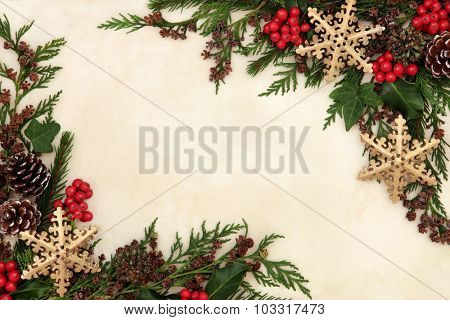 Christmas background border with gold snowflake bauble decorations, holly, ivy and winter greenery over old parchment paper.