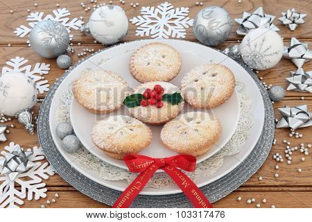 Mince pies, merry christmas ribbon, bauble decorations and holly over oak background.