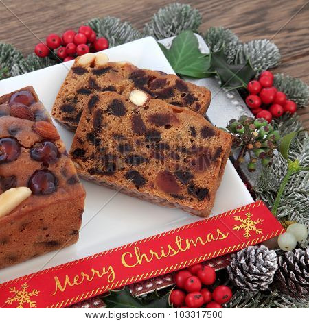 Genoa cake and slice with merry christmas ribbon, holly and winter greenery over oak background.
