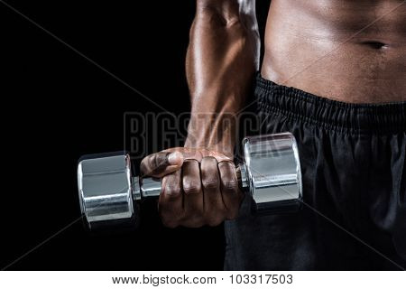 Cropped image of athlete exercising with dumbbell against black background