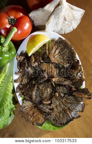 Grilled Mushrooms With Lemon On A Plate, With Ingredients On The Table