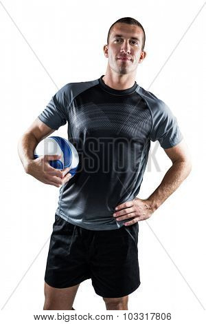 Portrait on rugby player holding ball with hand on hip against white background