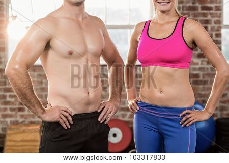 Fit models facing the camera in crossfit gym