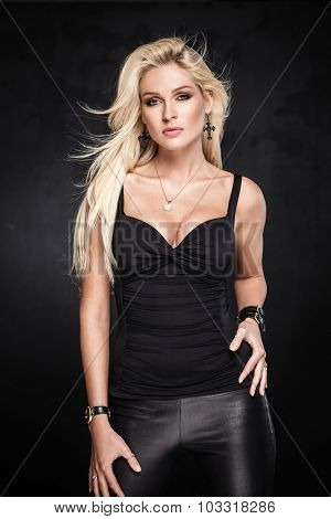 Sexy blond woman posing on dark background