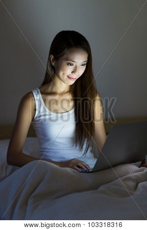 Woman working over night with laptop computer and sitting on bed