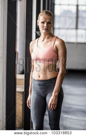 Muscular serious woman facing the camera in crossfit gym