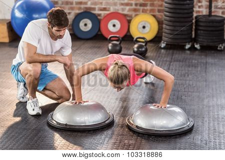 Male trainer assisting woman doing push ups in crossfit gym